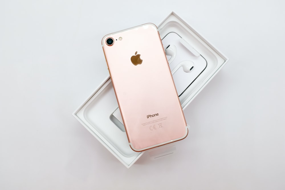 rose gold iPhone 7 with AirPods and box on white surface