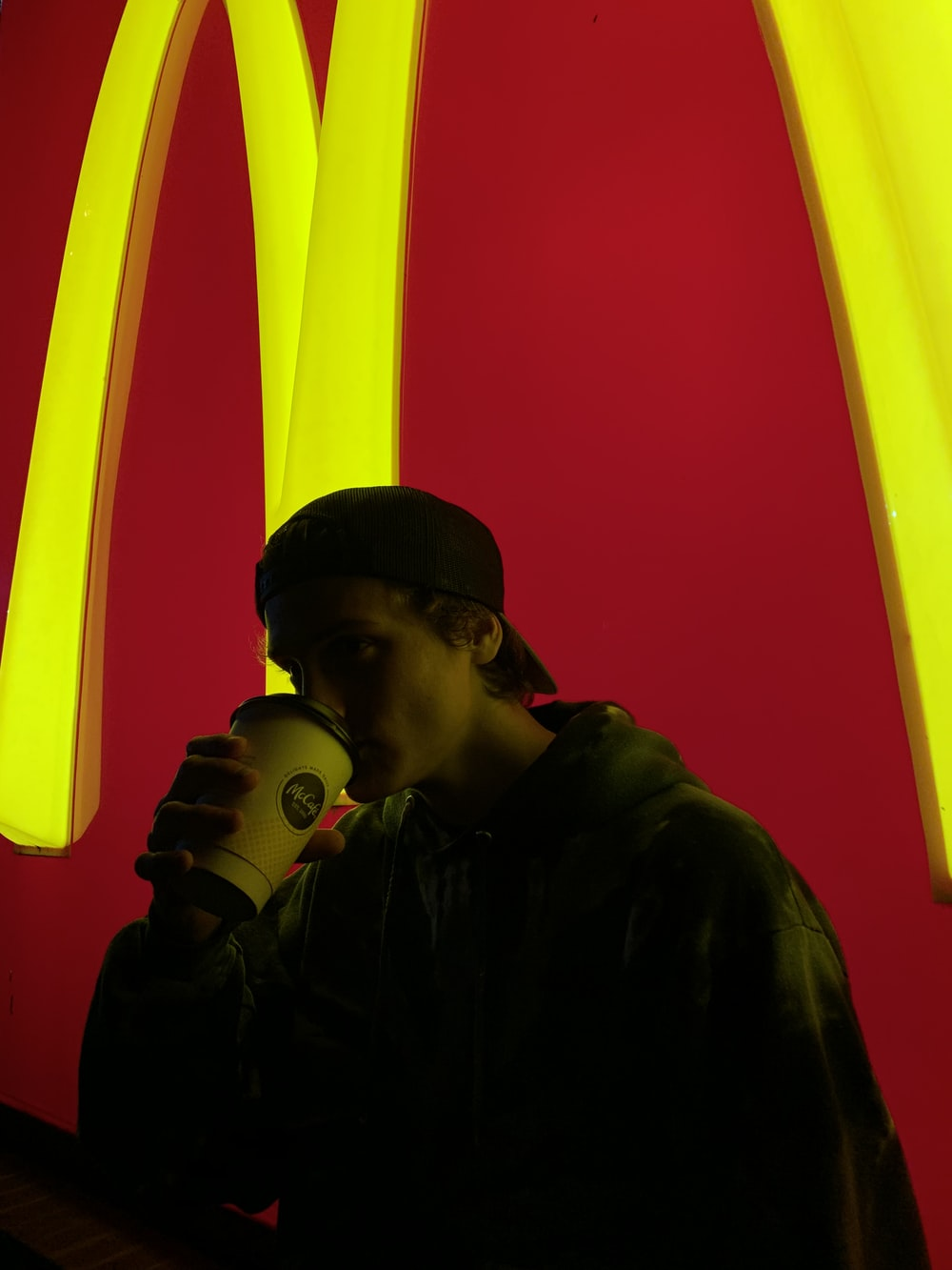man drinking on disposable cup