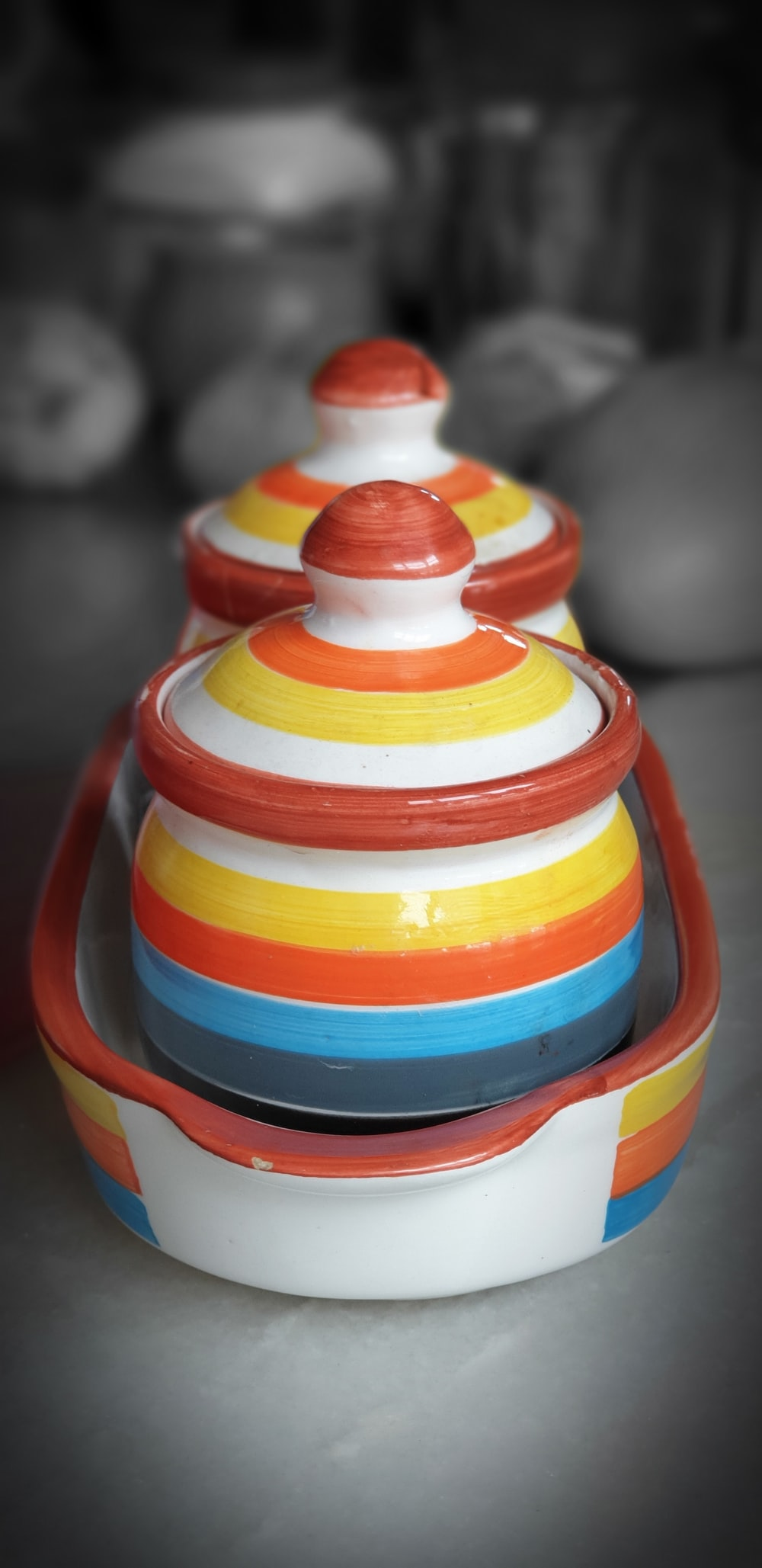 two multicolored ceramic canisters