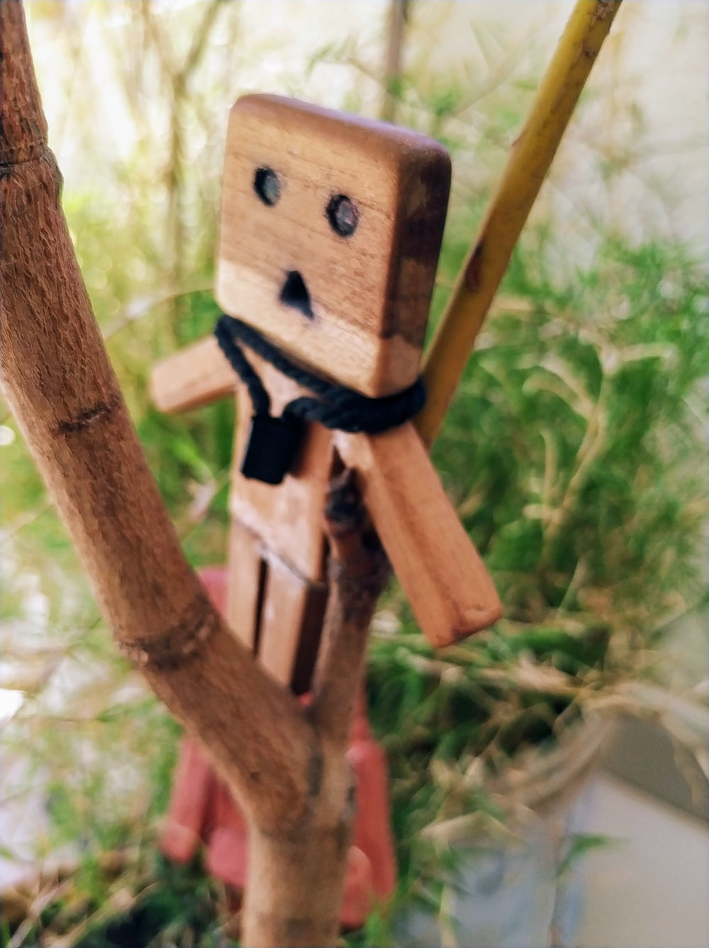 brown wooden character toy on wooden twig