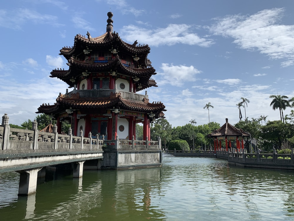 red and white temple near body of water