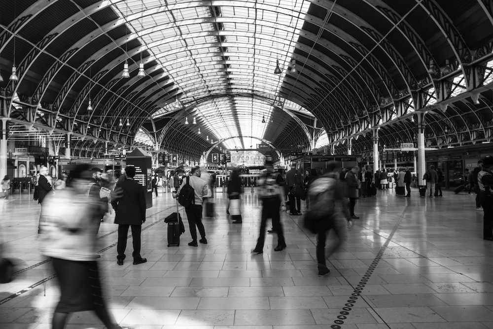 grayscale photo of people inside train station