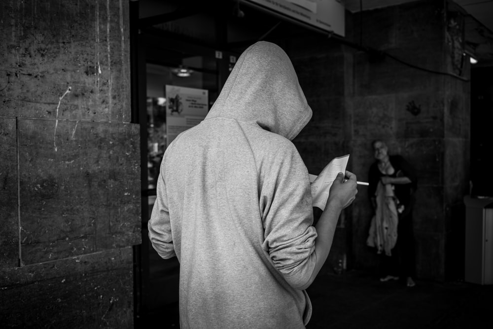 person in grey hoodie standing near wall