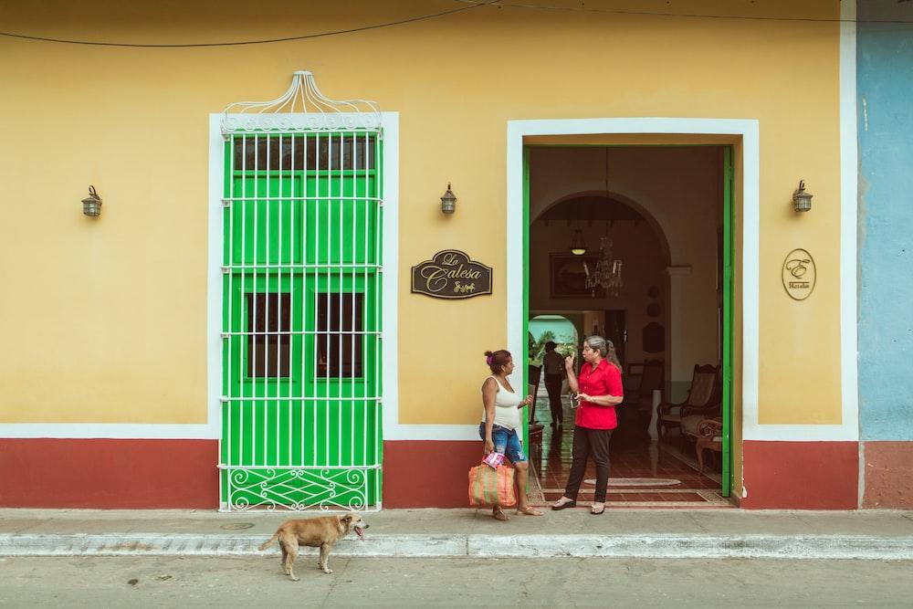 two women standing beside the doorway near dog