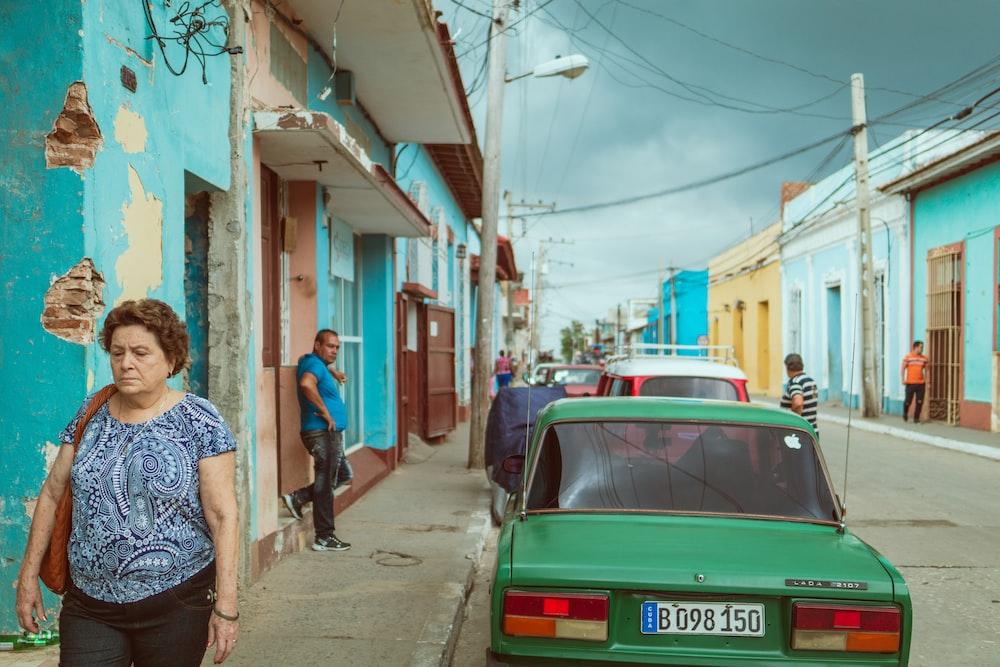 woman walking beside green vehicle during daytime
