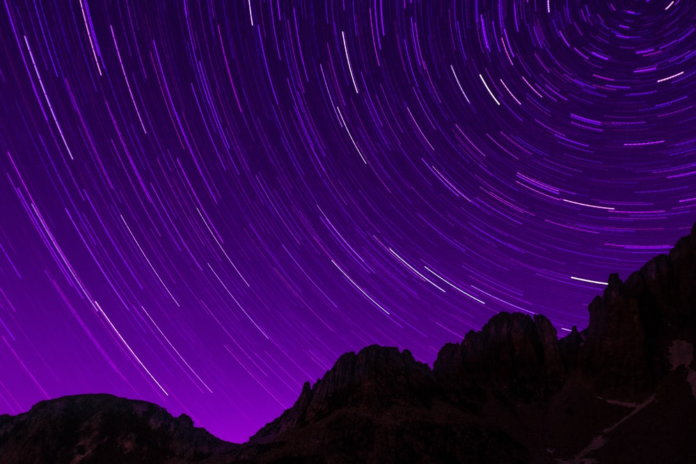 silhouette photography of mountain under galaxy