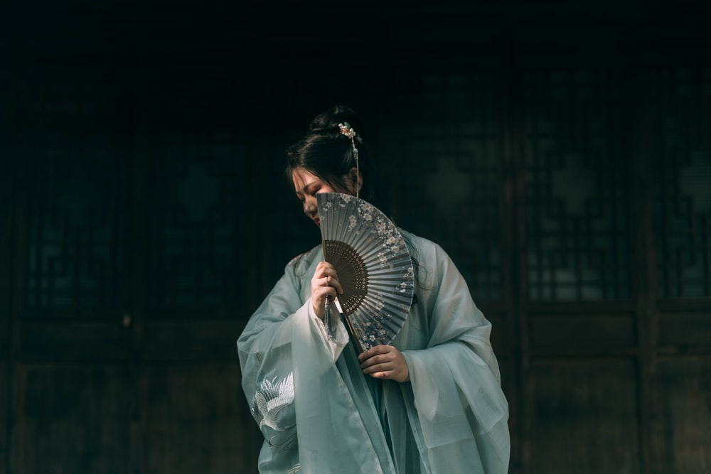 woman covering her cheek with hand fan