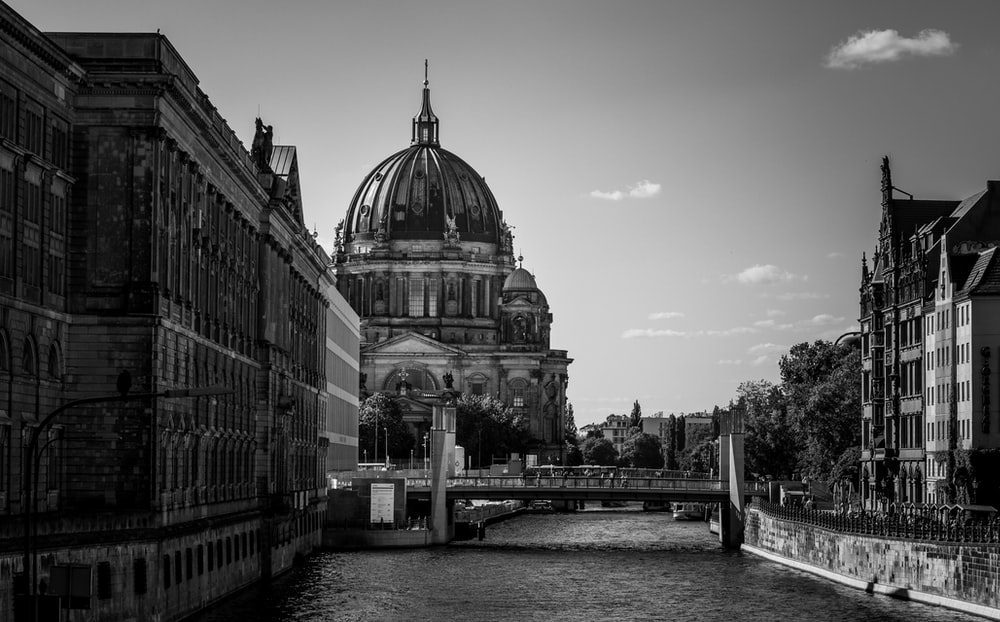 grayscale photography of buildings near body of water
