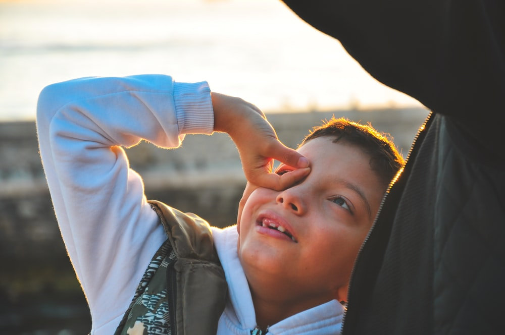 boy twisting his hand and puts on top of his eye