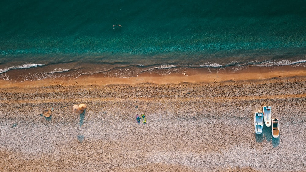 aerial photography of three boats parked on shore