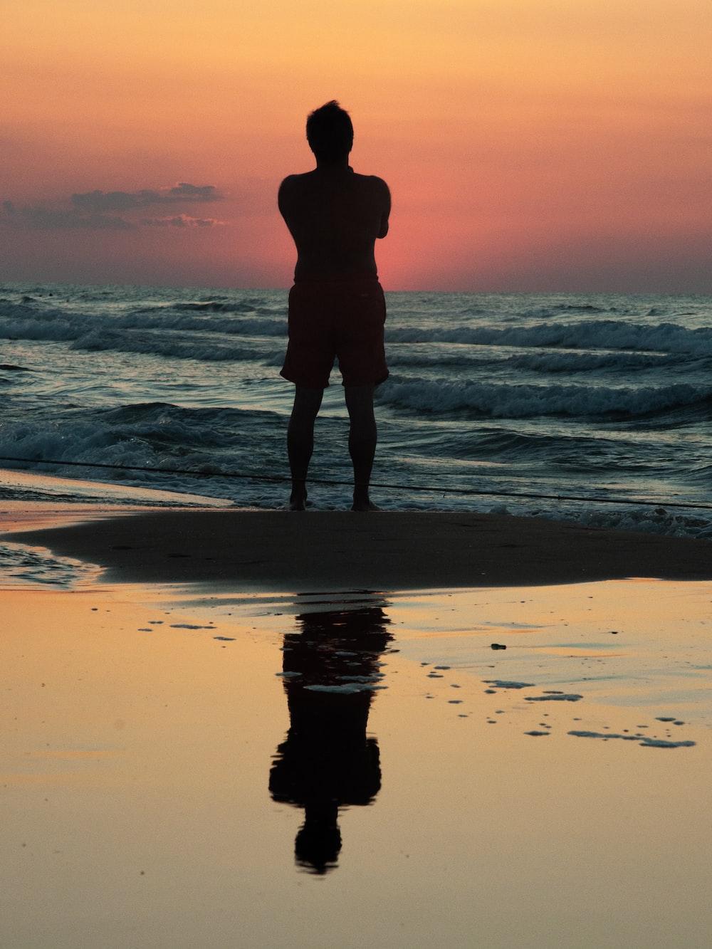 topless person standing near seashore