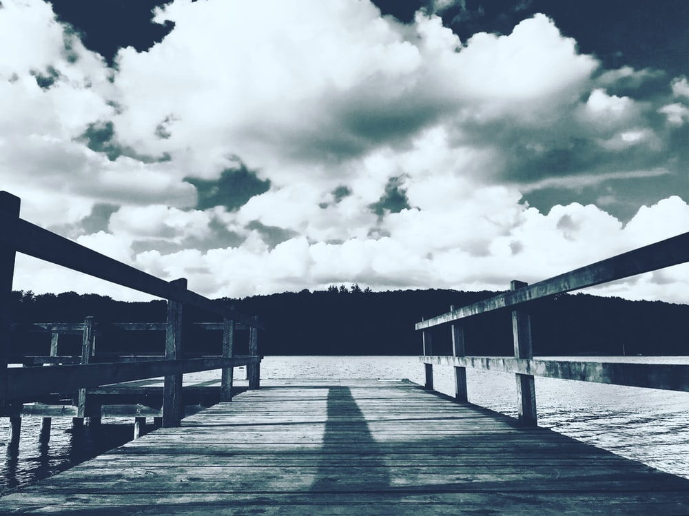 grayscale photography of boardwalk under cloudy sky