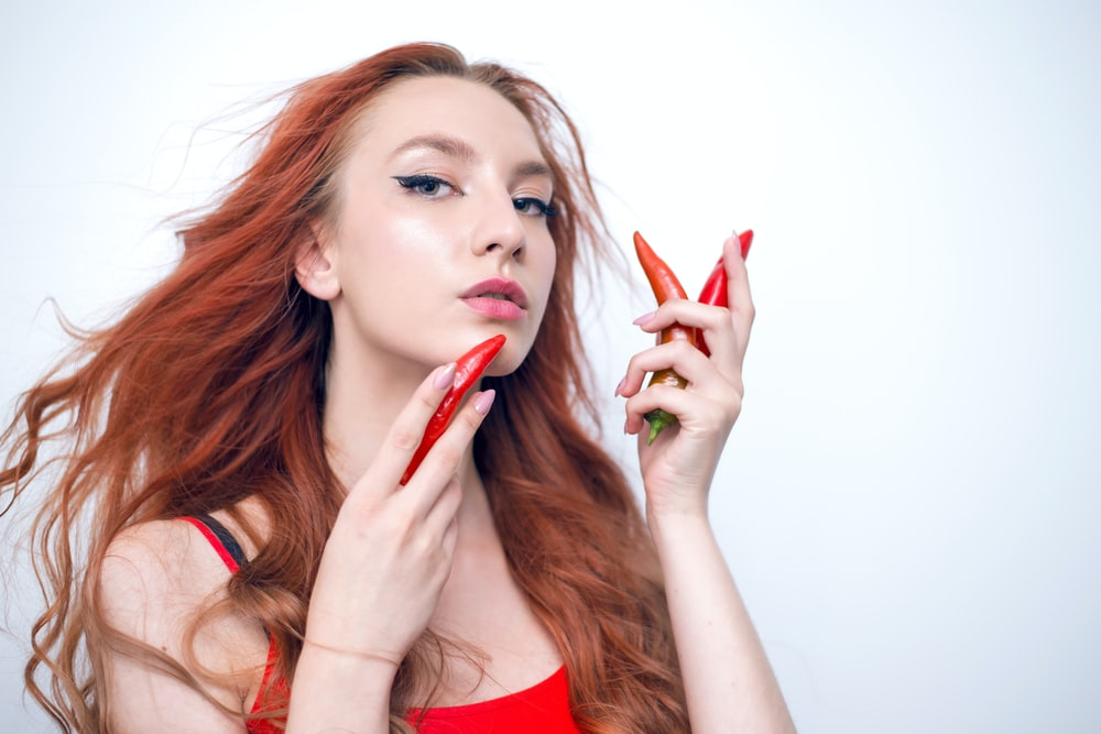 woman holding red bell pepper taking selfie