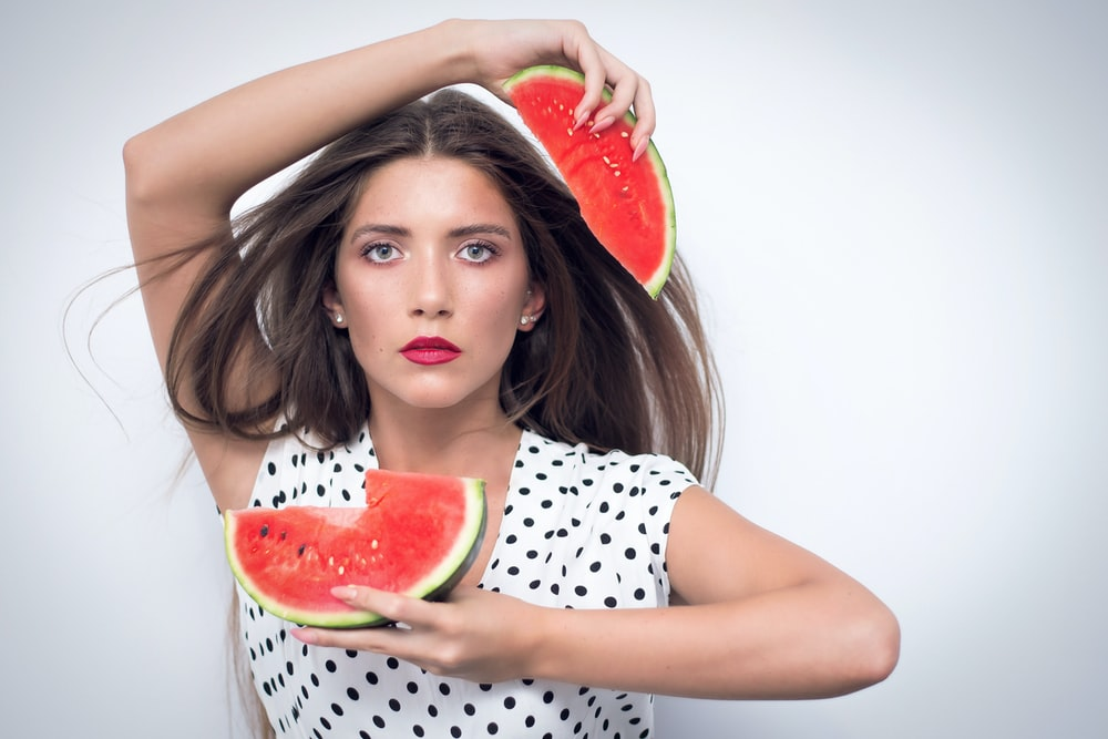 woman holding two pieces of watermelon