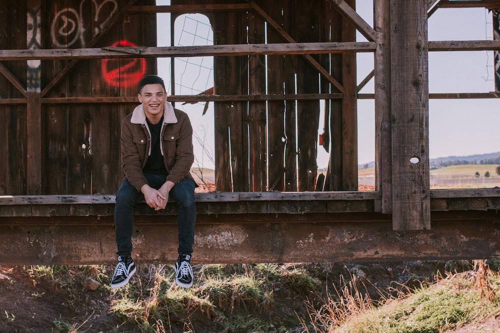 smiling man sitting on pavement