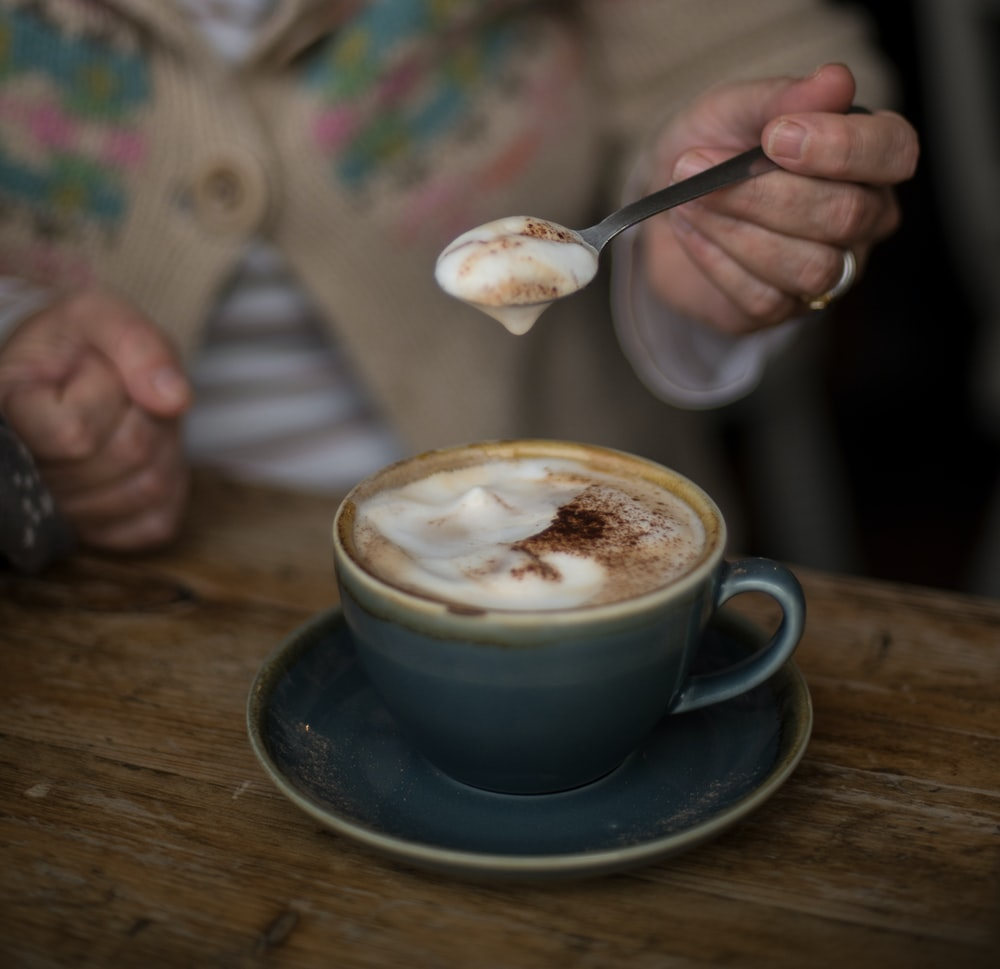 selective focus photography of person holding spoon with coffee