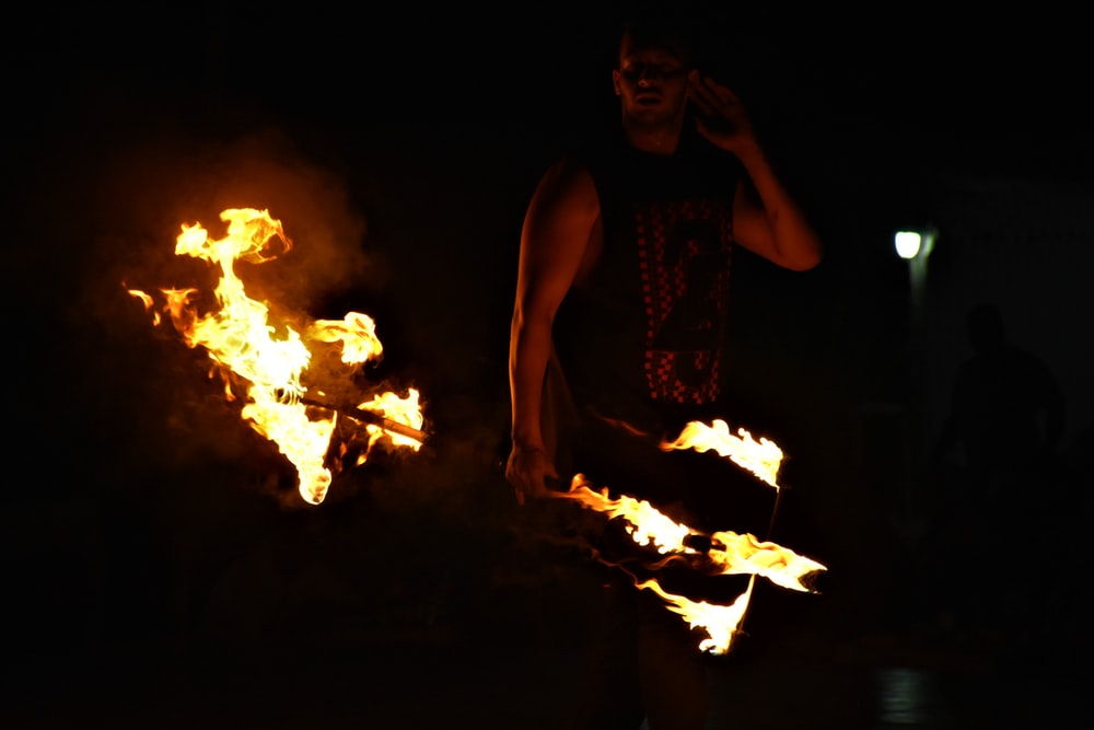 man holding fire rod during nighttime