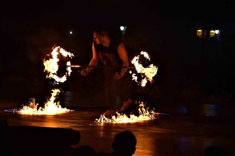 man performing fire dance with rod during nighttime