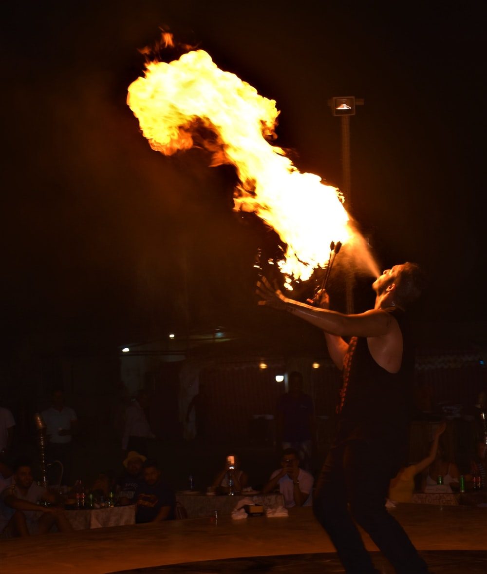 man performing on stage with fire breath