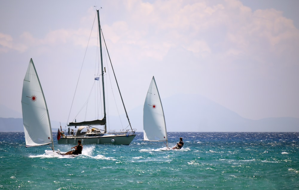two men windsurfing past anchored yacht at sea