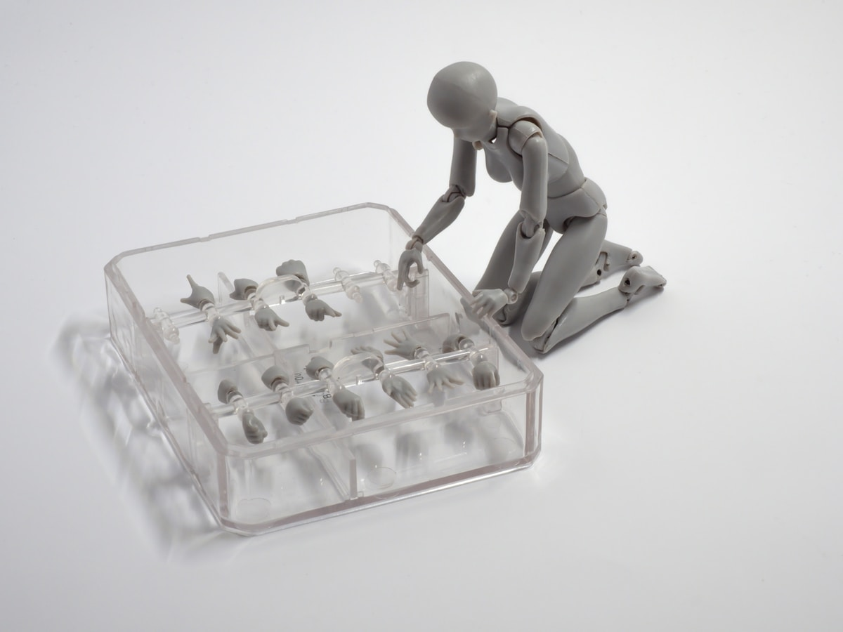 Image shows a drawing mannequin choosing from a selection of hands in a glass case.
