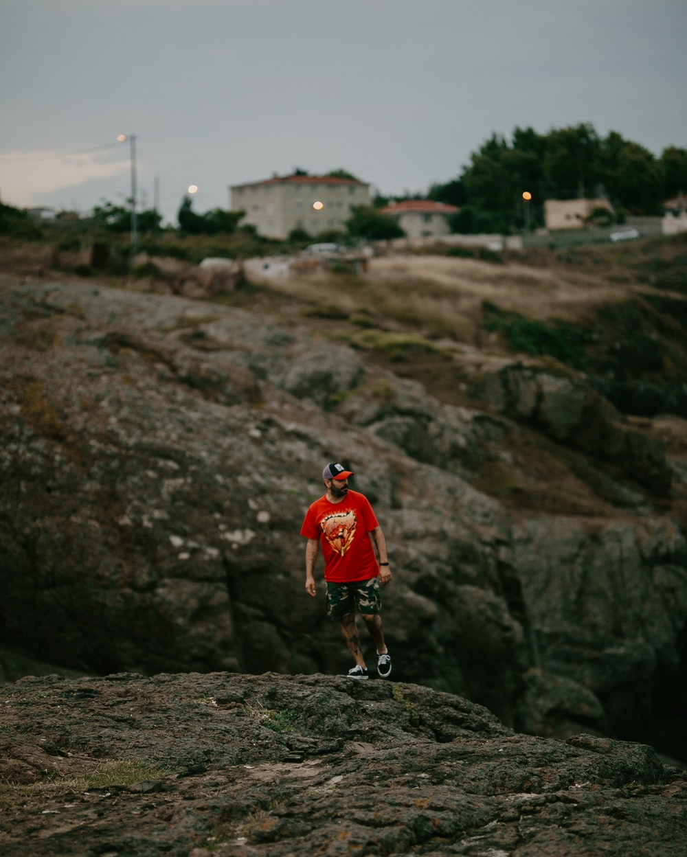 man in red t-shirt, green shorts and black fitted cap standing on rock hill