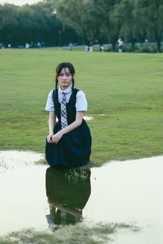 woman wearing black dress sitting beside body of water