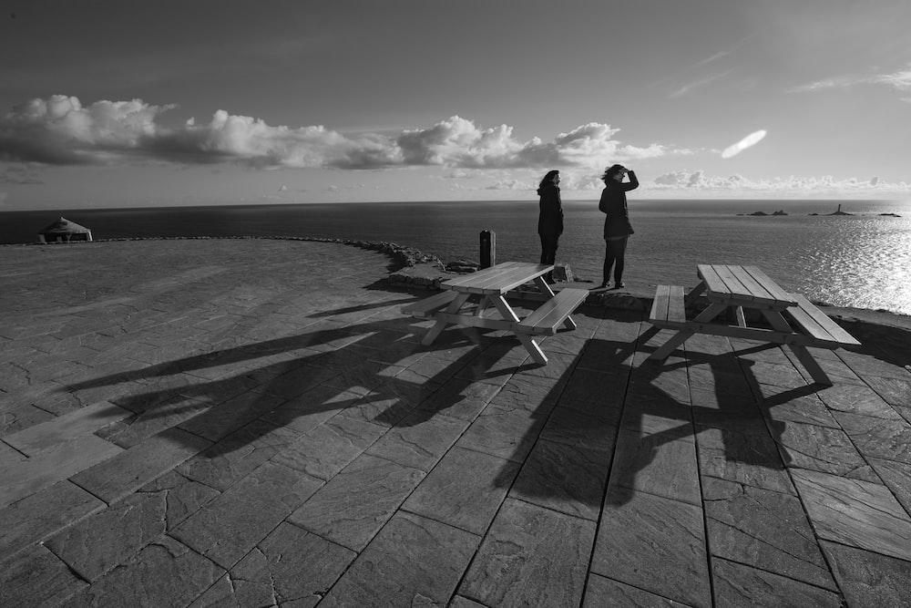two women standing near ocean