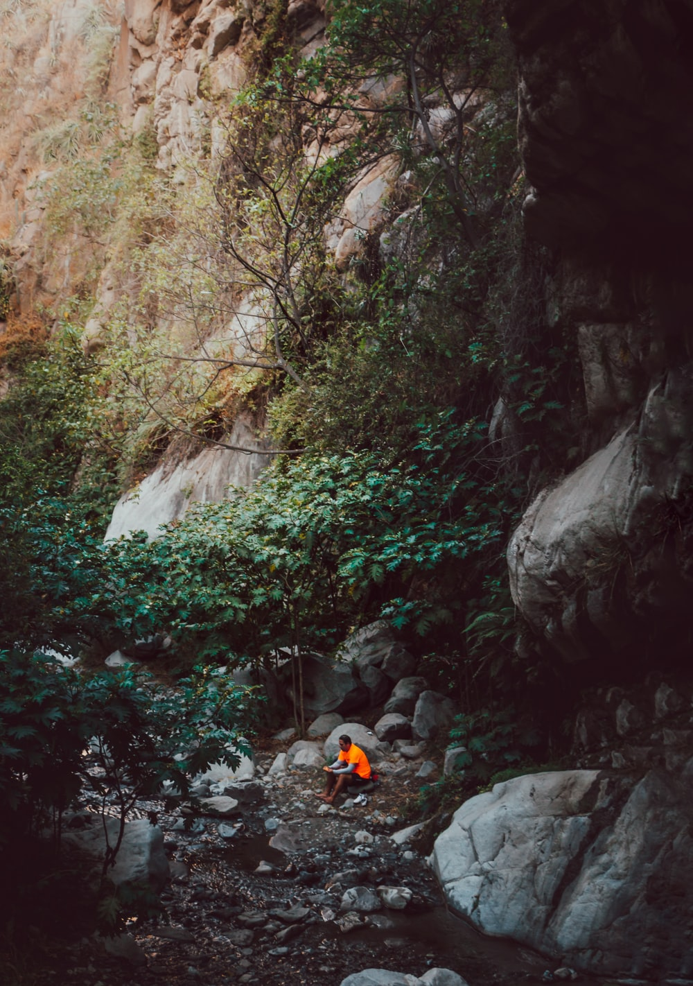 person sitting near a cave during daytime