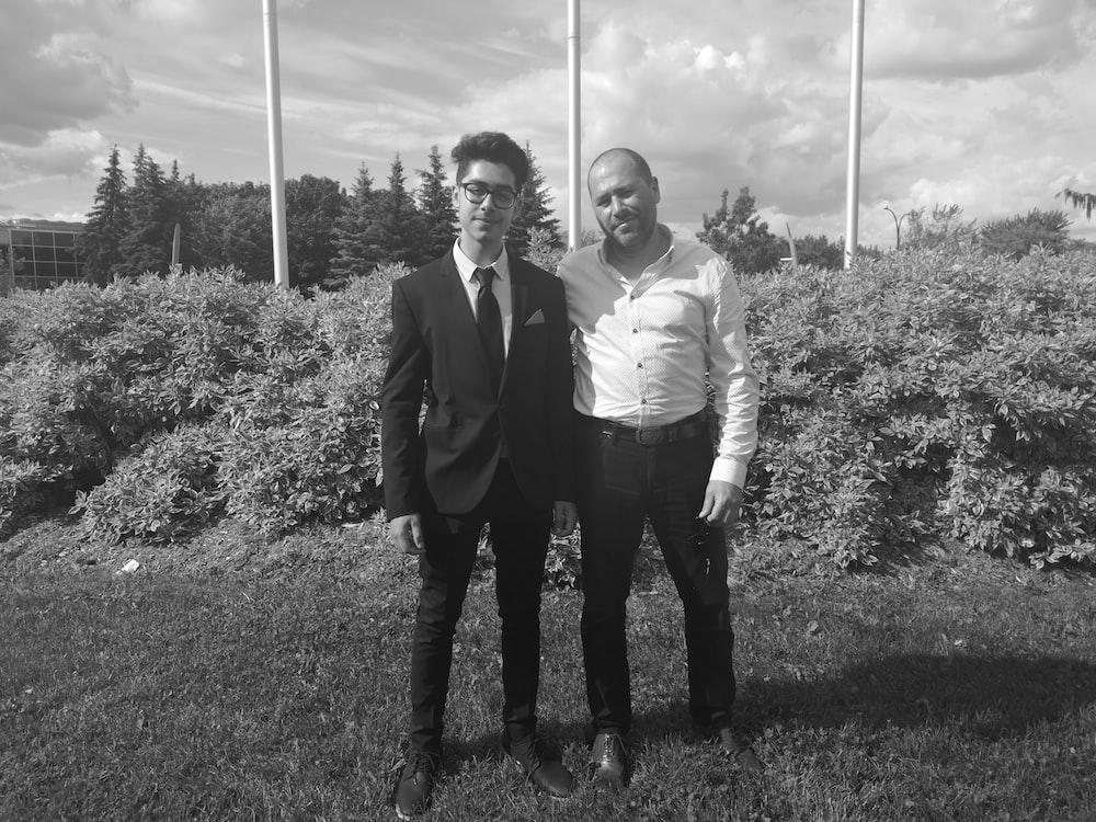 two men standing near plants