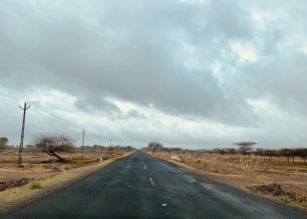 black asphalt road under cloudy sky during daytime