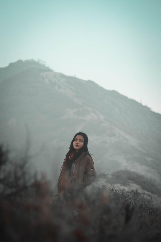 woman wearing jacket near mountainss