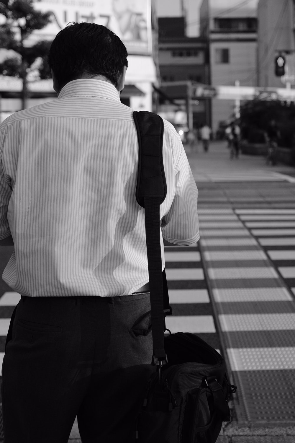 grayscale photography of man carrying bag