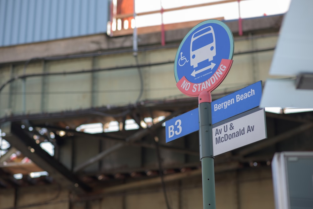blue and red no standing on bus road signage
