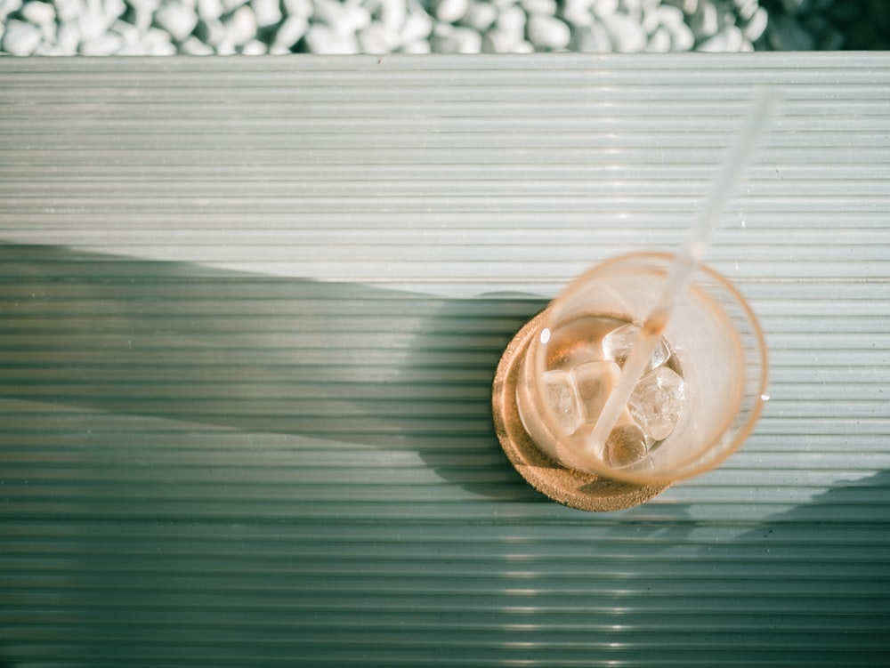 flat lay photography of glass with ice cubes and straw