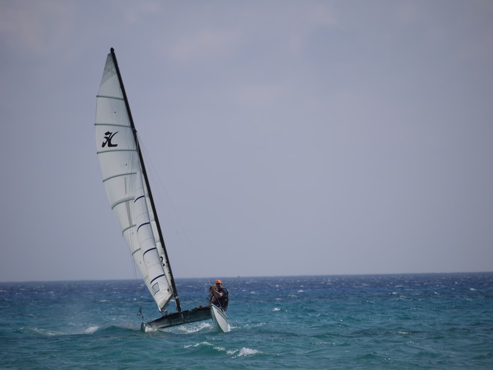 two men riding a sailboat in the sea