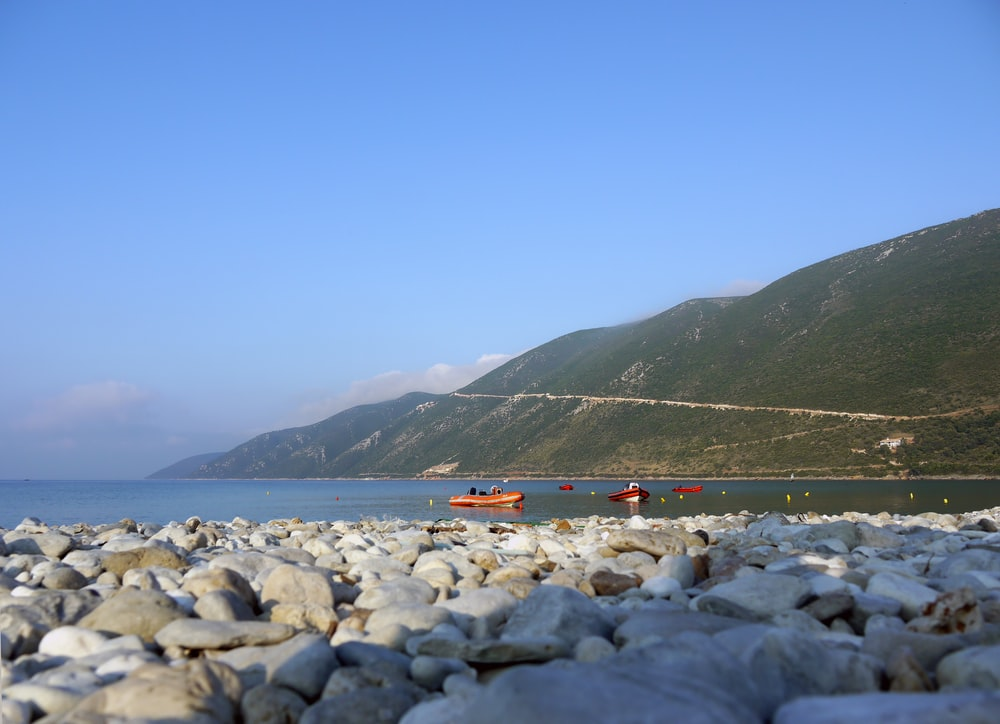orange boat in beach during daytime