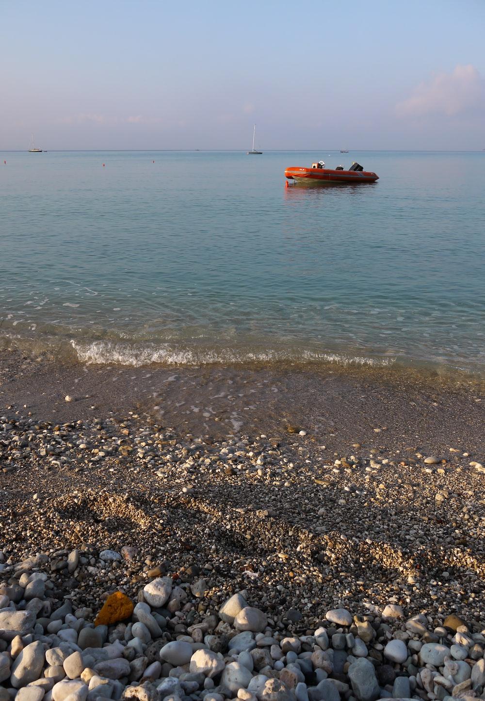 orange raft on body of water