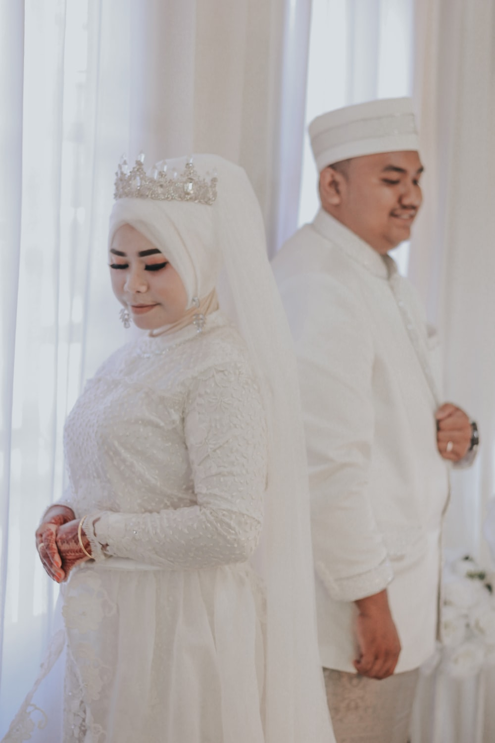 man and woman in wedding attire standing in room