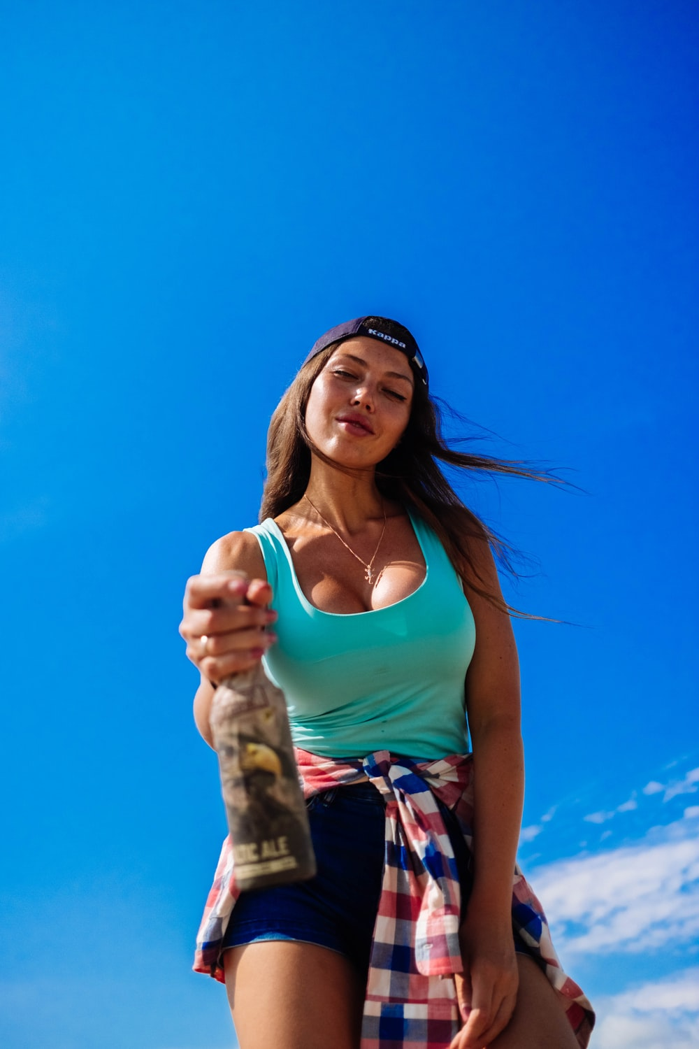 woman wearing blue tank top holding bottle under white clouds and blue sky during daytime