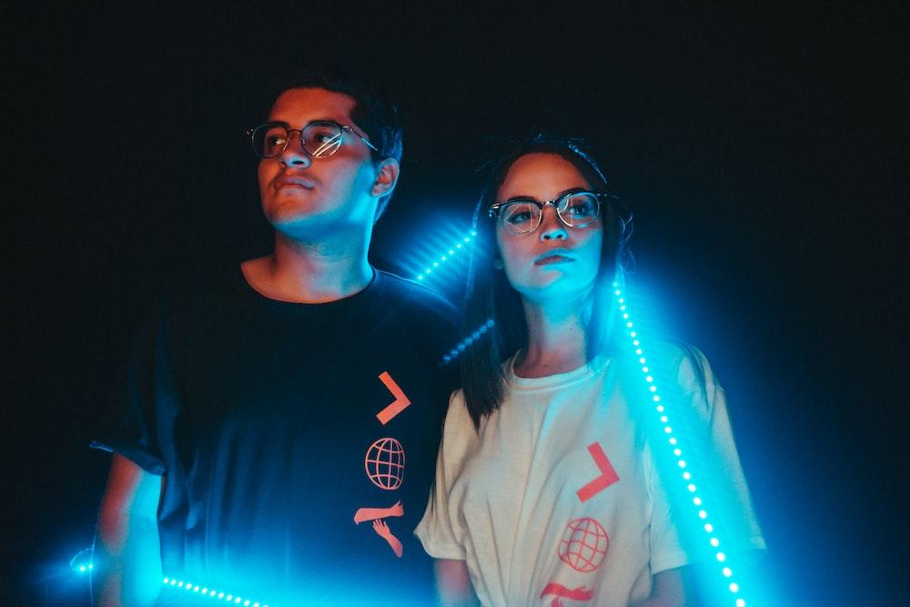 couple standing near neon light