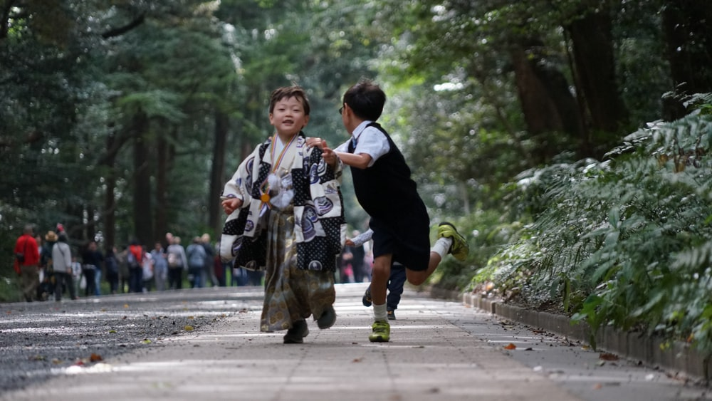 two boys running at the street during daytime