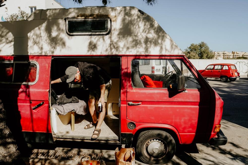 man standing inside van during daytime