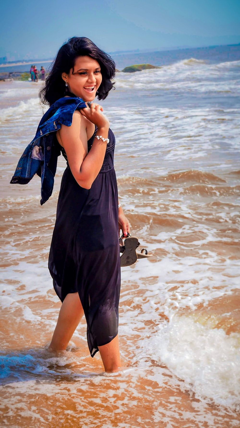 woman in purple sleeveless dress standing at the shore