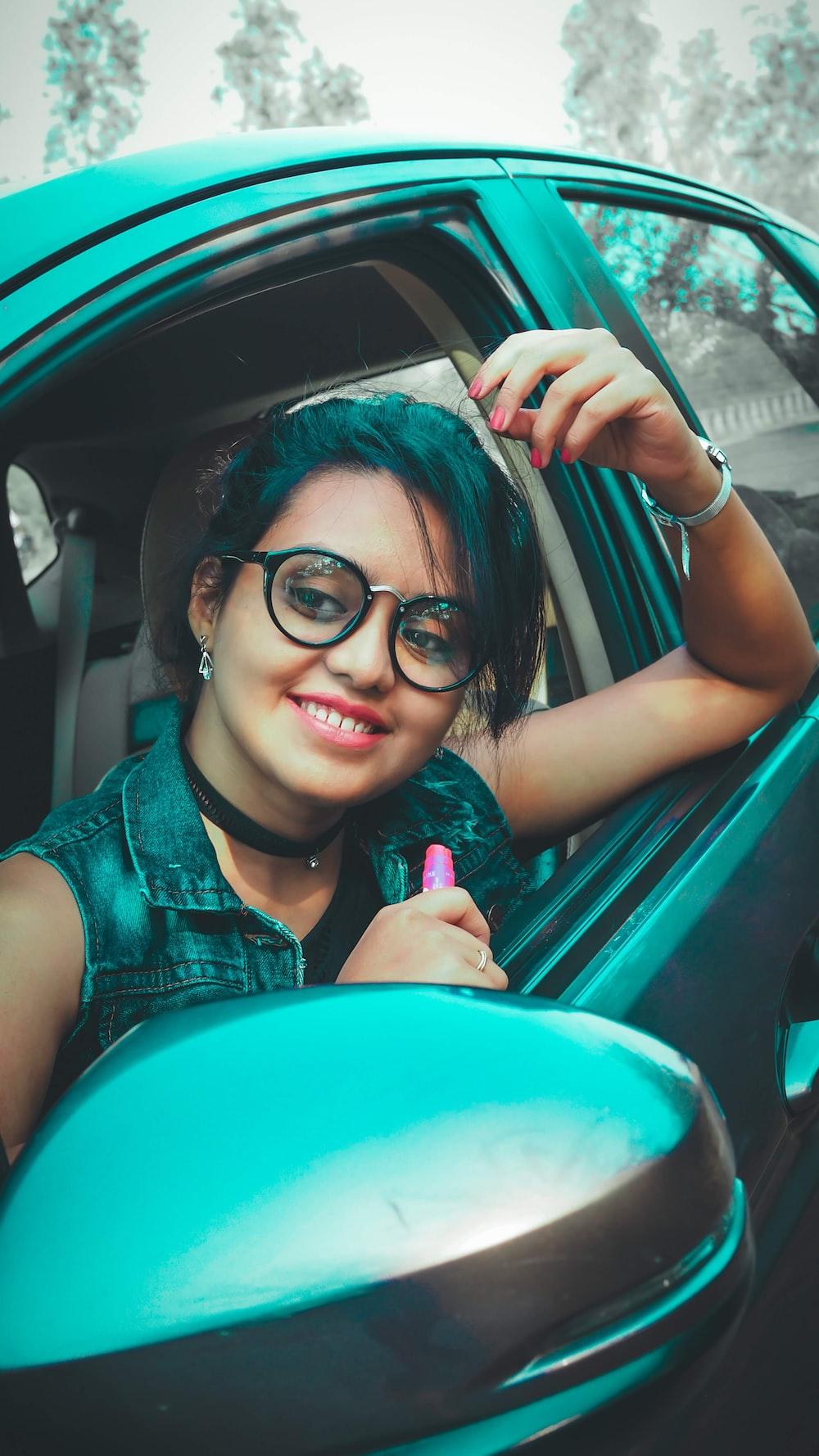 smiling woman wearing eyeglasses sitting inside vehicle\