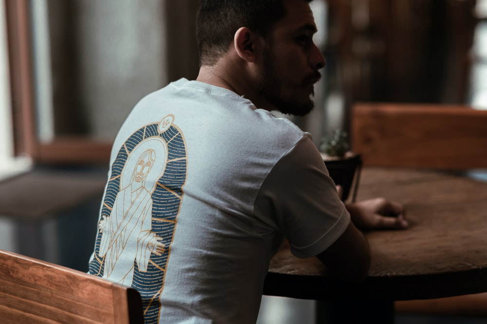 man in white t-shirt sitting at the table