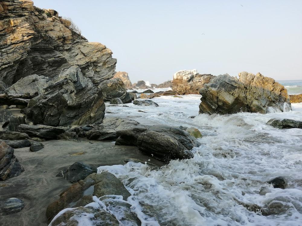 photography of ocean wave crashing on brown rock during daytime