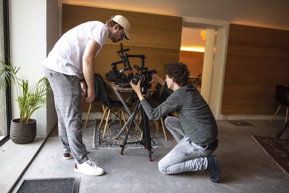 two men setting up camera in room