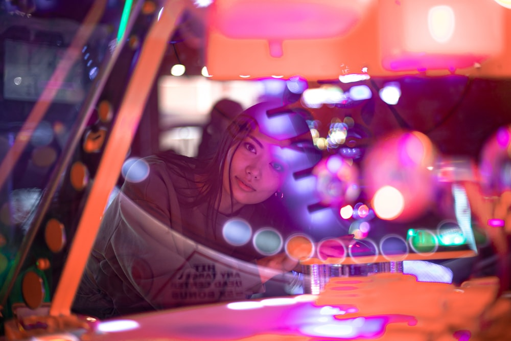 woman standing near arcade machine