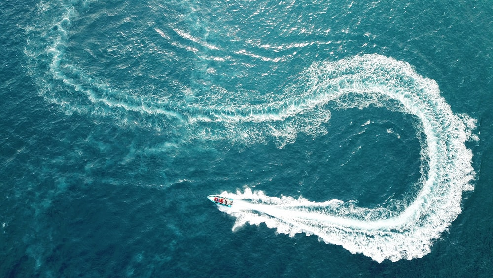 aerial photography of boat making zig zag way on body of water